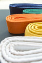 Judo and karate colored belts from white to blue Stock Photos