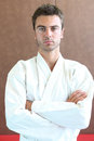 Judo practe enthusiast standing on a mat with his arms folded Royalty Free Stock Images