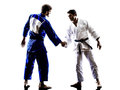Judokas fighters fighting handshake men silhouette two in on white background Royalty Free Stock Photos