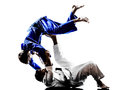 Judokas fighters fighting men silhouettes two in on white background Royalty Free Stock Photos
