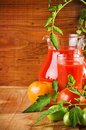 Jug and glass with tomato juice and tomatoes Royalty Free Stock Photo