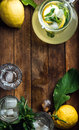 Jug with homemade lemonade, mint, fresh lemons and ice cubes on wooden background, top view, copy space