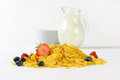 Jug of milk and corn flakes with fruits Royalty Free Stock Photo