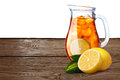 Jug or pitcher of iced tea with lemons on foreground standin on Royalty Free Stock Photo