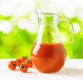 Jug of tomato juice on nature background half full pitcher Royalty Free Stock Images