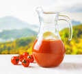 Jug of tomato juice on nature background half full pitcher Stock Photo