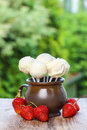 Jug of white cake pops fresh strawberries around summer garden party Royalty Free Stock Photo