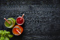Juice bar three colorful juices with straws on dark wooden surface Royalty Free Stock Photo