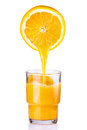 Juice being poured into a glass of orange sliced on white background Stock Photography