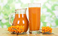 Juice from  berries of sea-buckthorn  on  green abstract background. Royalty Free Stock Photo