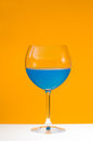 Juice glass of blue beverage on orange background Royalty Free Stock Photo