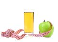 Juice and green apples measured the meter white background Royalty Free Stock Image