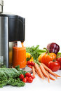 Juice making a juicer surrounded by healthy fruits and vegetables on white with shadows Stock Photo