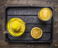 Juicer and a glass of juice with sliced oranges in a wooden tray wooden rustic background top view close up Royalty Free Stock Photo
