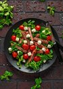 Juicy Beef Sirloin Steak Salad with roasted tomatoes, feta cheese and green vegetables in a black plate. healthy food Royalty Free Stock Photo