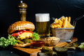 juicy cheeseburger with fries, pickles, beer and coleslaw salad served by bistro Royalty Free Stock Photo
