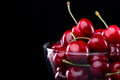 Juicy cherries in a bowl shiny glass on black background Royalty Free Stock Images