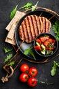 Juicy grilled chicken meat lula kebab on skewers with fresh vegetable salad on black background Royalty Free Stock Photo