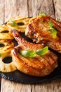 Juicy grilled pork chop in honey glaze served with pineapple and Royalty Free Stock Photo