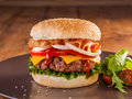Juicy hamburger a charcoal broiled with bacon onion rings tomato cheddar cheese and vegetables Stock Image