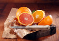 Juicy oranges one whole and some sliced in halves on brown paper with knife Stock Photo