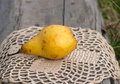 Juicy pear on the placemat yellow crocheting lacy Royalty Free Stock Photo