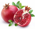 Juicy pomegranate and its half with leaves. Royalty Free Stock Photo