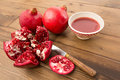 Juicy pomegranates fresh and cut on a wooden table Royalty Free Stock Photos