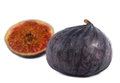 Juicy ripe purple fig with a whole fresh and halved portion in the foreground Royalty Free Stock Images