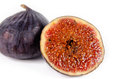 Juicy ripe purple fig with a whole fresh and halved portion in the foreground showing the texture of the seeds Royalty Free Stock Photo