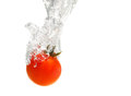 Juicy small cherry tomato dropped in water isolated on white Royalty Free Stock Image