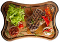 Juicy steak from marbled beef with vegetables on a wooden board. Isolated