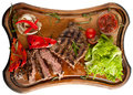 Juicy steak from marbled beef with vegetables on a wooden board. Sliced. Isolated