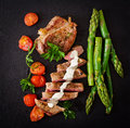 Juicy steak medium rare beef with spices and tomatoes, asparagus Royalty Free Stock Photo