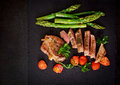 Juicy steak medium rare beef with spices and tomatoes, asparagus. Royalty Free Stock Photo