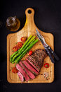 Juicy steak rare beef with spices on a wooden board and garnish of asparagus. Royalty Free Stock Photo