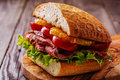 Juicy steak sandwich with vegetables and slices of orange. Royalty Free Stock Photo