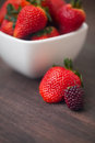 Juicy strawberry in a bowl and blackberry on a wooden surfa red surface Royalty Free Stock Photography