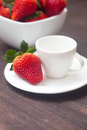 Juicy strawberry in a bowl and cup on a wooden surface red Royalty Free Stock Photo