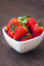 Juicy strawberry in a bowl on a wooden surface red Royalty Free Stock Images