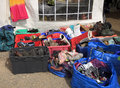 Jumble sale boxes and bags of used and second hand clothing boots and for outside a charity shop Royalty Free Stock Image