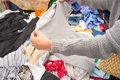 Jumble sale hand rummaging in a heap of clothes at a Royalty Free Stock Photo