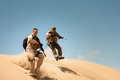 Jump for cover two heavily armed special forces officers over the bank in pursuit Stock Images