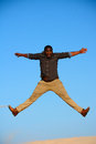 Jump for joy full body front view of an african american man with happy facial expression stretching out arms and legs while Royalty Free Stock Images