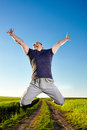 Jump for joy in the wheat field young man jumping over a rural road crossing a Royalty Free Stock Photography
