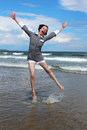 Jump for joy a young girl jumps into the air on the beach Royalty Free Stock Images