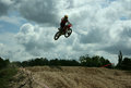 Jump motocross rider jumping high at a Royalty Free Stock Image