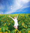 Jump among sunflowers beautiful young woman in white sundress jumps on flower field under blue cloudy sky Royalty Free Stock Images