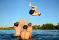 Jump into water active young men jumping it rescues from an overheat on the hot sun rays river karaidel black river one of the Stock Images