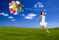 Jumping with a colored ballons beautiful woman running and on green meadow Stock Images